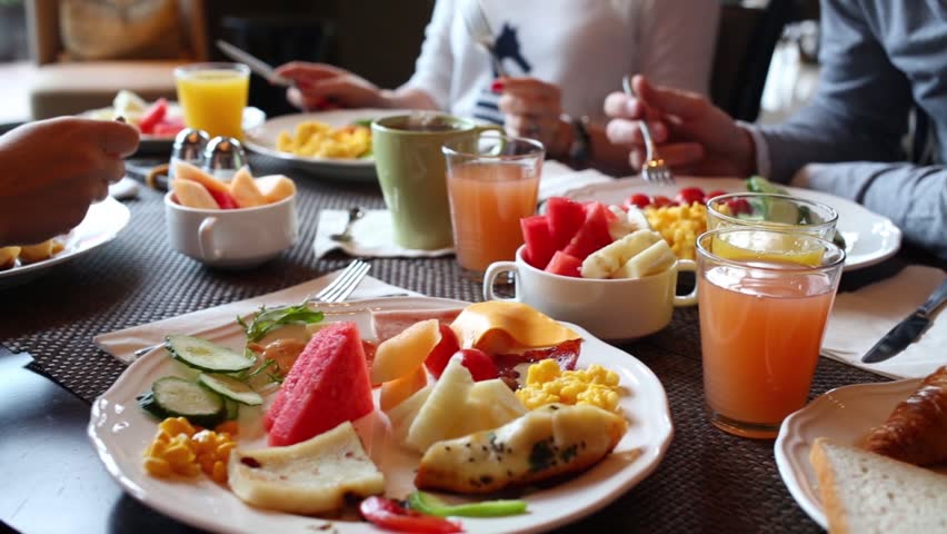 Table with food and glasses of juice, hands of eating people | Shutterstock Video #18785828