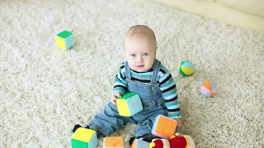 Baby boy playing on the floor and looking at camera