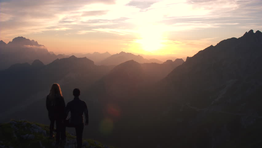 Aerial - Flyover hiking couple watching beautiful sunset in the mountains