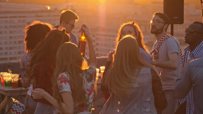 Group of multi-ethnic young people drinking beer, dancing to the music played by dj and raising their arms up in the air at sunset party on city rooftop | Shutterstock Video #19079275