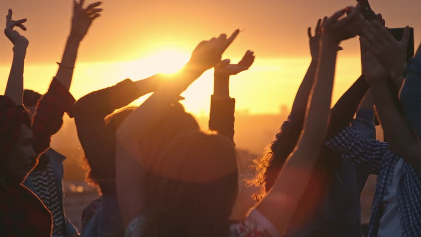 Group of young multi-ethnic people having fun dancing with raised arms to the music played by dj at rooftop party at sunset