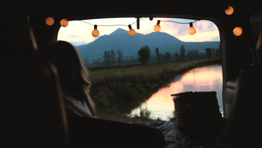 A young woman admiring the sunset in the trunk of a car decorated with twinkle lights. | Shutterstock HD Video #19199248