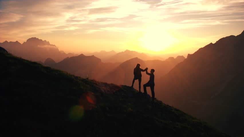 Aerial, edited - Silhouette of a couple giving each other a high five celebrating successful climb on the mountain in beautiful sunset