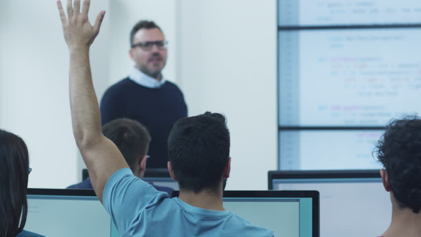 Male Student Raising Hand to Answer a Question During Lecture in Computer Class. Shot on RED Cinema Camera in 4K (UHD).