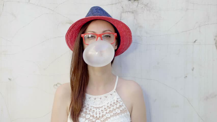 Hipster girl blows big bubble from bubble gum...