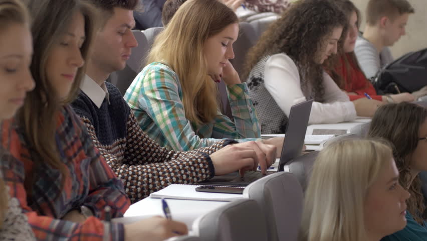 A lot of college students listening in a lecture and taking notes. Young motivated people studying a subject in the lecture theatre. | Shutterstock HD Video #19441264