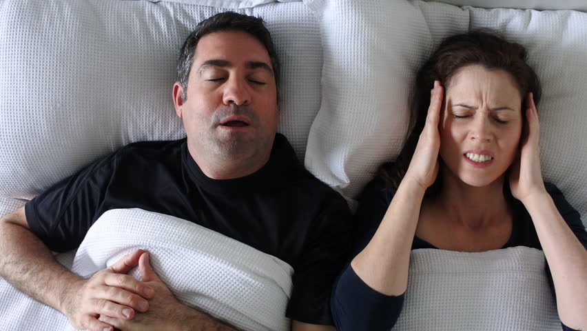 Woman (age 30-40) suffers from her partner (age 35 - 45) snoring in bed. Couple lifestyle and people health care concept. Real people copy space