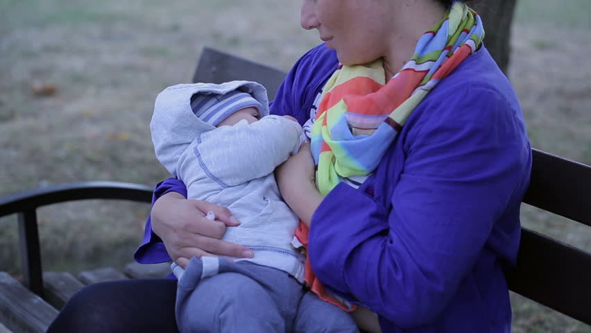 Video Bench Part - 39: Mother Is Breastfeeding, Sitting On A Bench At The Park - HD Stock Video  Clip
