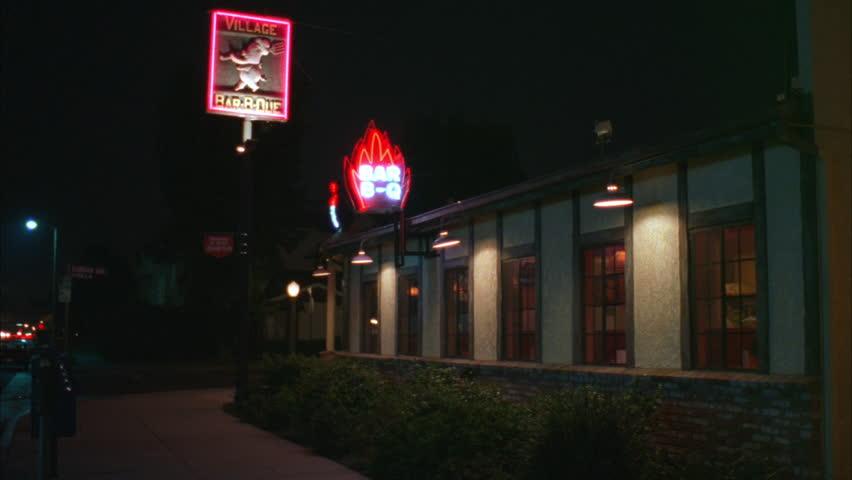 night Side Raked right Village Bar B Que neighborhood BBQ restaurant 1 story white stucco bldg w brick brown accents