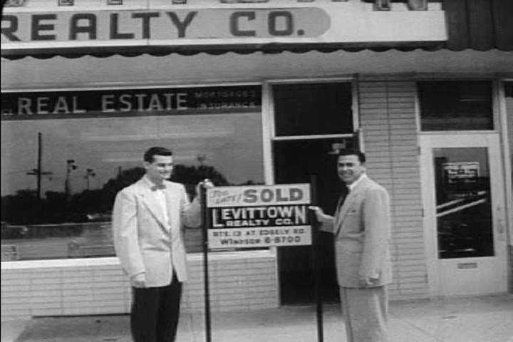 Real estate agents work in their office, and hammer a sold sign into a yard in Levittown, PA in the 1950s. (1950s)