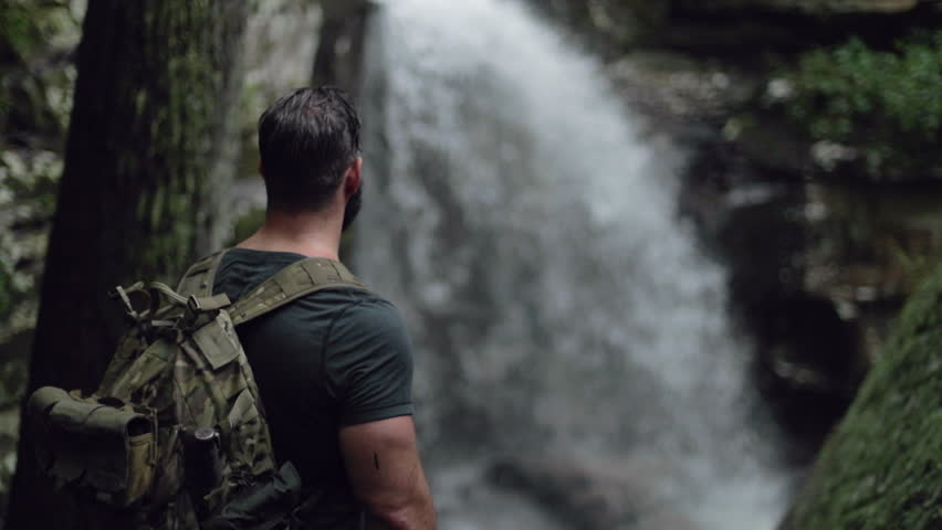 A male hiker watches a waterfall in slow motion.