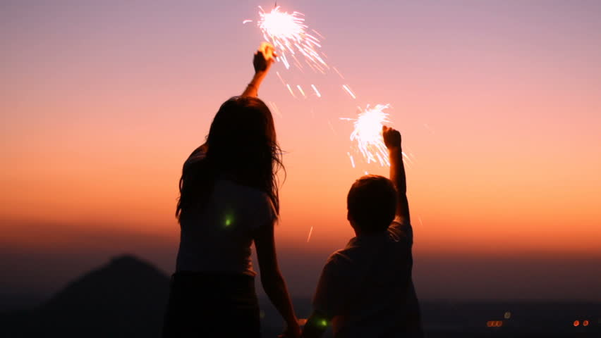 A young mother with a son at sunset celebrate holding sparklers | Shutterstock HD Video #19730938