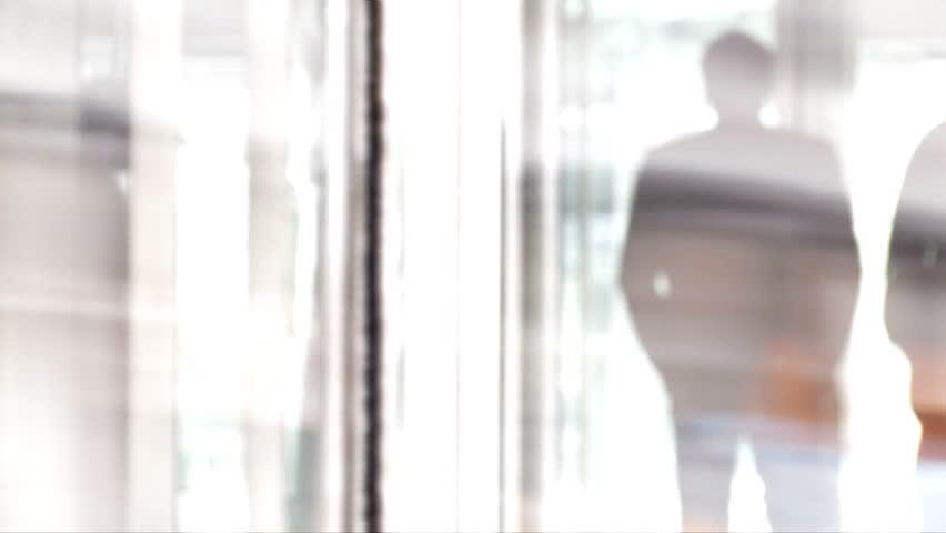 Businessman reflection in glass rotating door