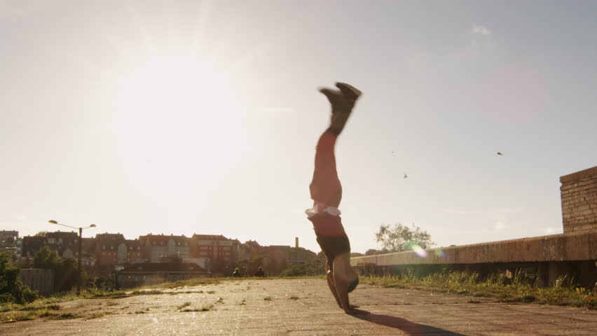 Young Male Freerunner Performing Acrobatic Elements Outdoors in Urban Environment. Shot on RED Cinema Camera in 4K (UHD).