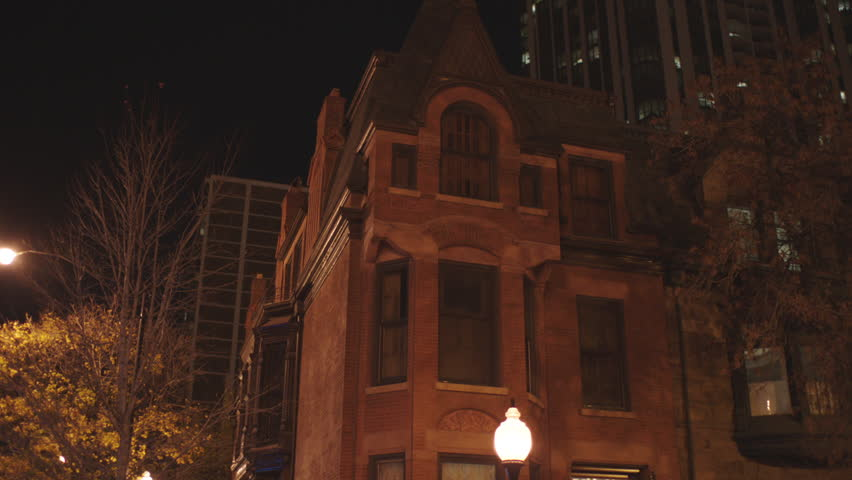 night hold up corner quaint ornate brick row house then tilt down , along small city street 3 story brick buildings cream white accents