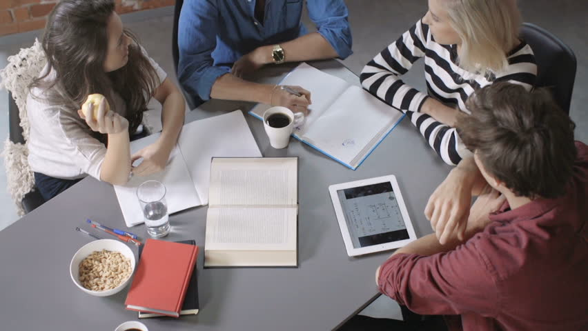Group of young people on the meeting in modern loft apartment. Four students working on their homework. Top view of diverse people in trendy office. Youth, education and technology concept. | Shutterstock HD Video #19991071