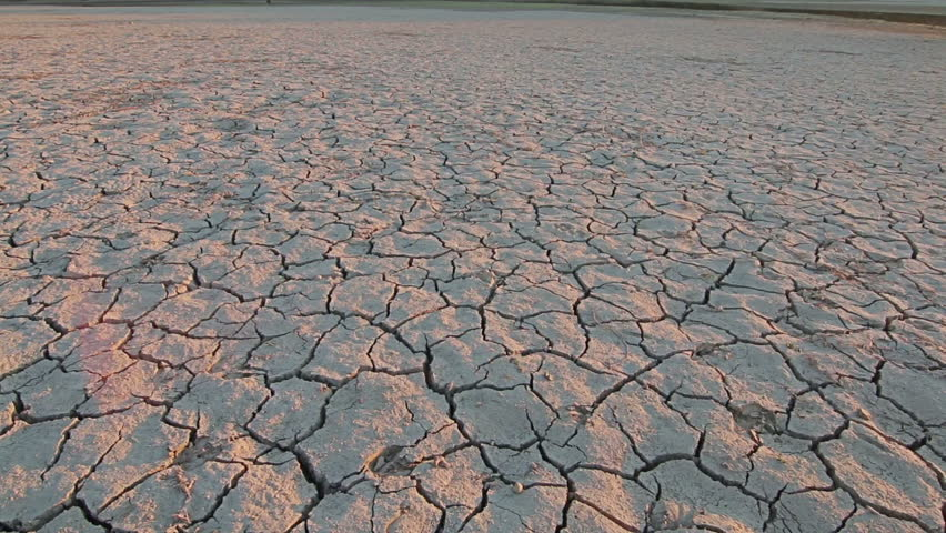 Sunset above drought disaster  dry soil  Climate change  global warming   HD stock. Dry Lake Bed With Natural Texture Of Cracked Clay In Perspective
