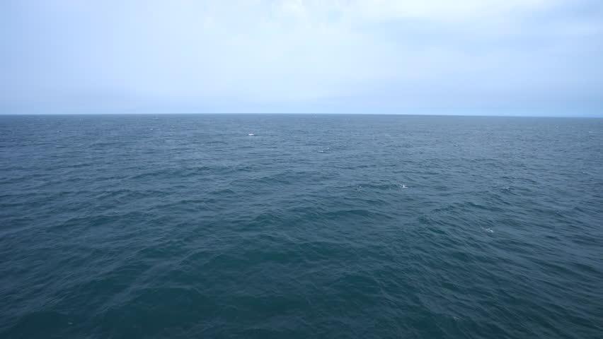 Aerial shot of open ocean. Blue sky and horizon.