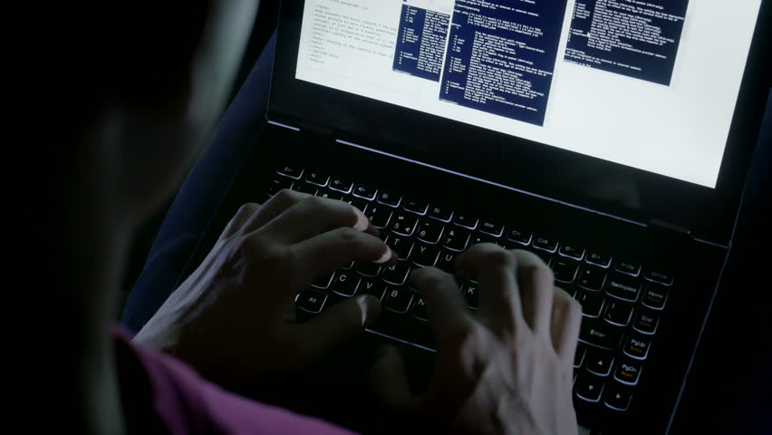 Close-up of hacker's hands typing codes on the keyboard. Young sly man trying to breach the system while giving bad commands in the dark.