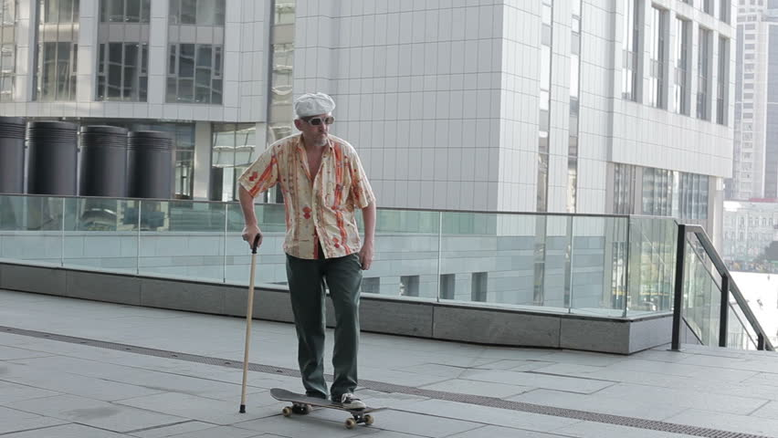 Old man with a cane riding on a skateboard. | Shutterstock Video #20348239