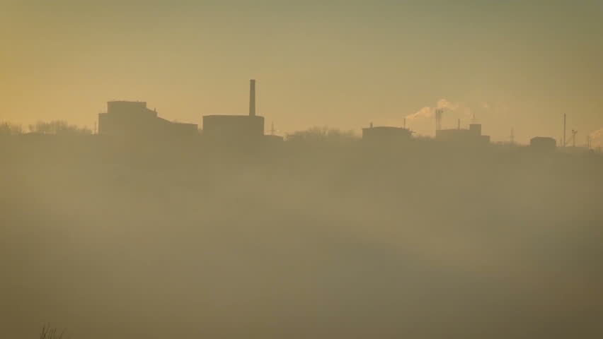 Industrial Area. Smoking, Polluting Factory Pipes.dust in the Air. Sunset. Almost Invisible Buildings in the Dusk
