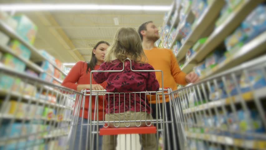 Beautiful young parents and their cute little daughter are smiling while choosing food in the supermarket. Girl is sitting in the shopping cart | Shutterstock HD Video #20534791