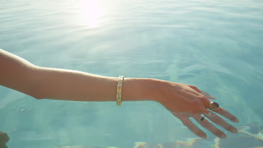 SLOW MOTION CLOSE UP: Unrecognizable young girl caressing water with soft hands and sliding with fingers on its surface on sunny summer day. Enjoying and relaxing in infinity pool at luxury resort
