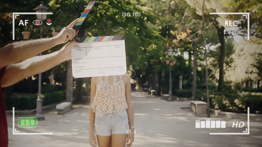 Seen through a camera viewfinder. A gorgeous girl on a movie set, a slate or clapperboard marks the start of the shooting. She smiles and comes close to the camera.