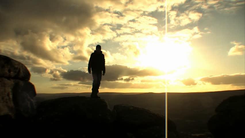 Figure Jumping Off Rocks - Silhouette Sunset   Shutterstock HD Video #2077715