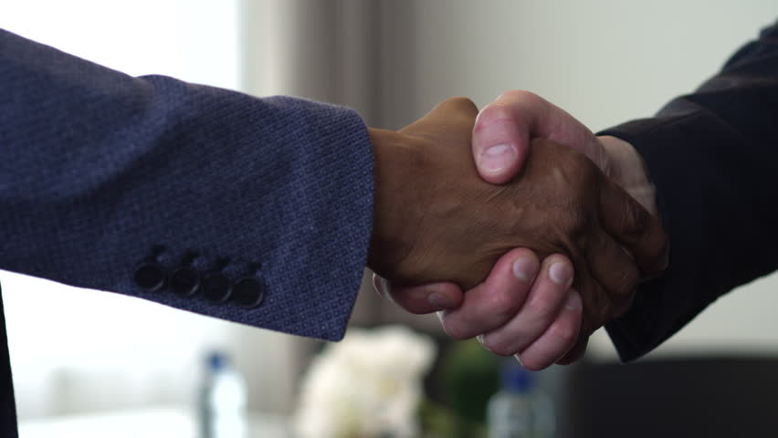 We see a handshake between two businessmen. The agreement between them had been reached. One of them is an African American/Handshake of Two Businessman - is the Completion of the Transaction   Shutterstock HD Video #20801821