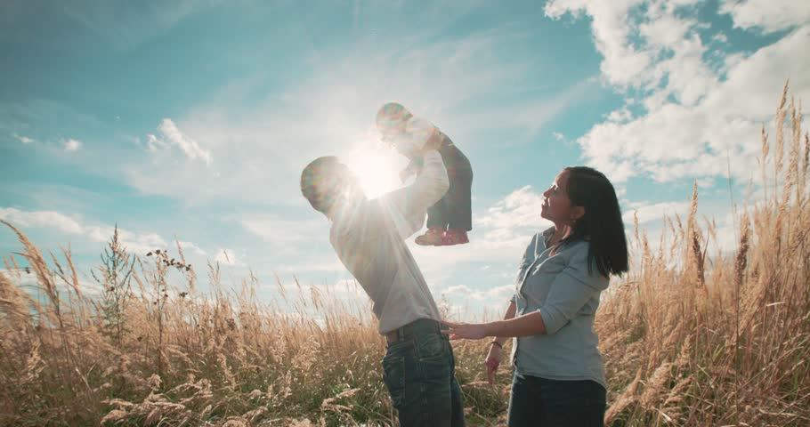young Asian family in a field with a baby 1 year on hand, the concept of family happiness, beautiful sunlight, sunset, slow motion