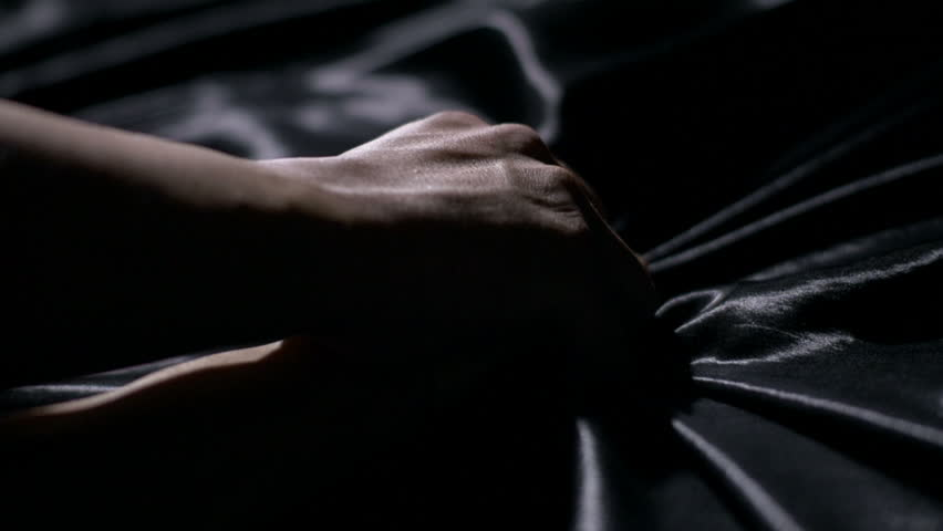 Making Love. Close-up of a man holding a woman's arms down in bed