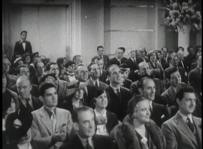 Wide shot of 1930s audience applauding