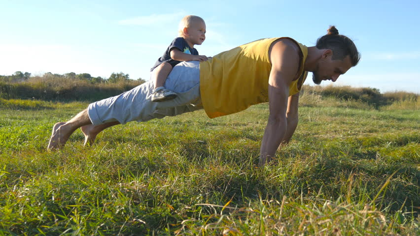 Young muscular father doing push ups with his little son on his back. Athletic man doing push-ups at green grass with happy smiling baby sitting on his rear. Strong guy spending time with your child