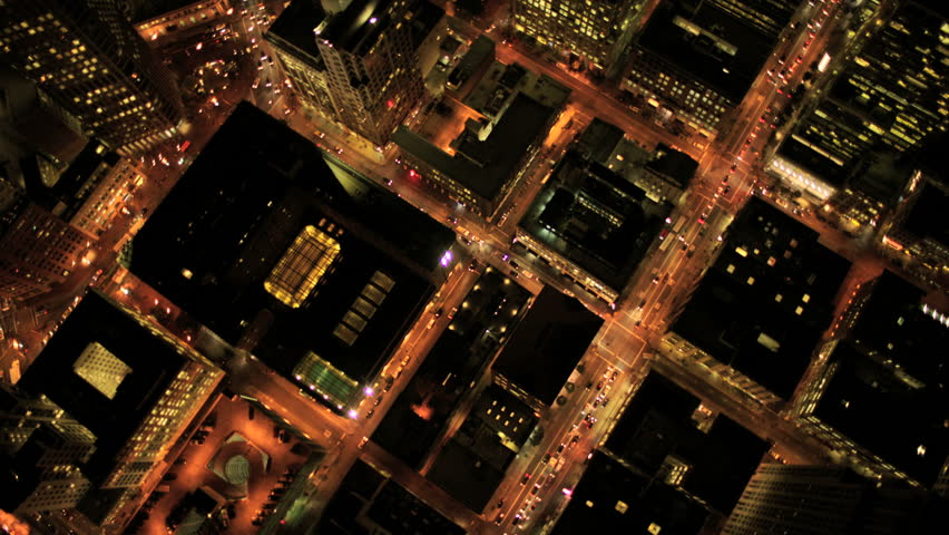Aerial night vertical view of skyscraper rooftops and illuminated streets in a modern city