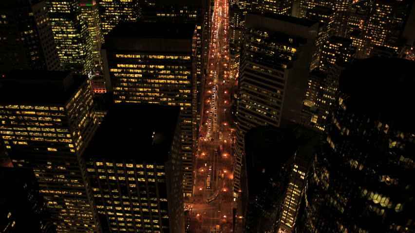 Aerial night illuminated view of skyscrapers, rooftops and city streets, North America, USA