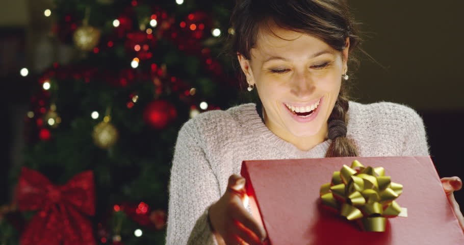 Girl with Christmas hat makes wishes and opens a Christmas gift package. concept of holidays and new year. the girl is happy and smiles with christmas gift in hand. | Shutterstock HD Video #21399469
