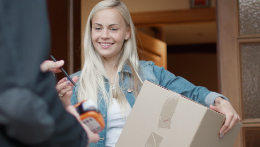Smiling Woman Receives Postal Package after Signing Electronic Signature Device while Standing in the Open Doorway. Shot on RED Cinema Camera in 4K (UHD).   Shutterstock Video #21531508