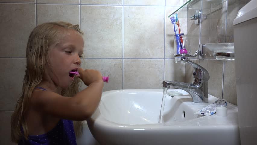4K Girl Brushing Teeth  Child Portrait Washing Using Toothbrush in Bathroom   4K stock footage. Ultra HD 4K Little Girl Brushing Her Teeth In Bathroom Before