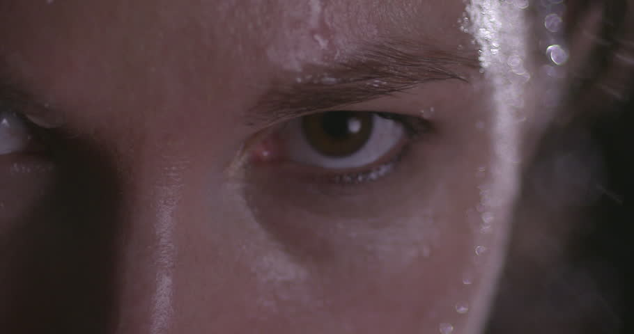 FEMALE BOXER WORKING OUT. Slow motion Extreme close up shot. A woman's left eye while she is breathing heavily