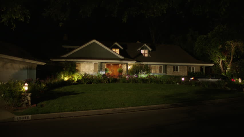 night one story house 2 dormer windows that can play two story house Nice landscaping accent lighting, circular driveway car pulls into driveway garage door opens it pulls