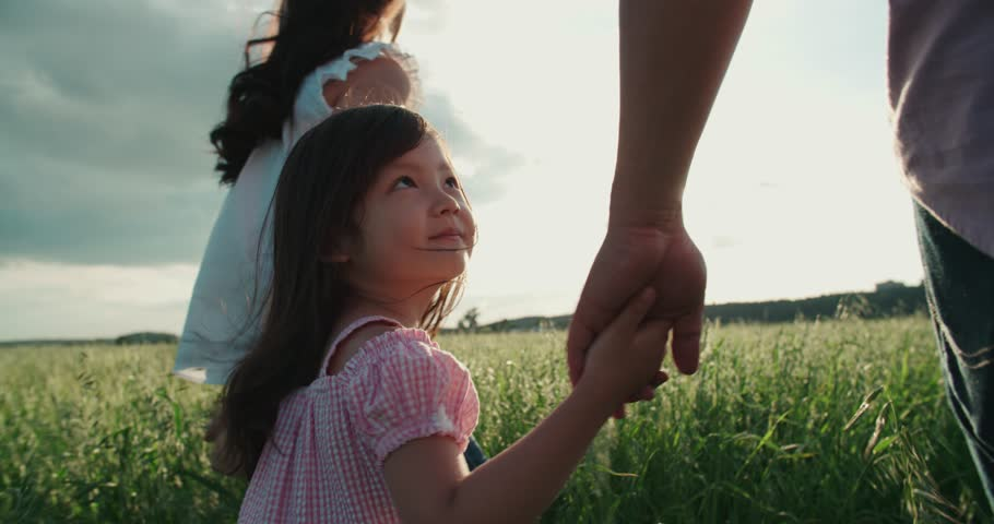 little Asian girl walking on the green field with their parents, holding the hand of his father, slow motion | Shutterstock Video #21874597