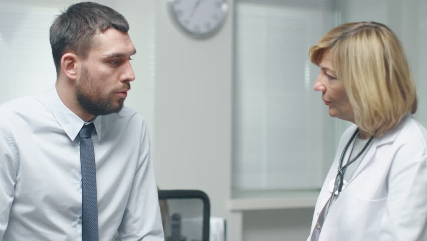Mid Adult Female Doctor Talks Seriously with Her Male Patient.  | Shutterstock HD Video #22022050