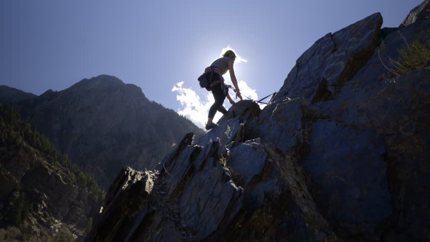 Adventurous Young Female Rock Climber Climbs To Top Of Peak, Gives Her Partner Below A Thumbs Up And Raises Her Arms In Victory   Shutterstock Video #22038928