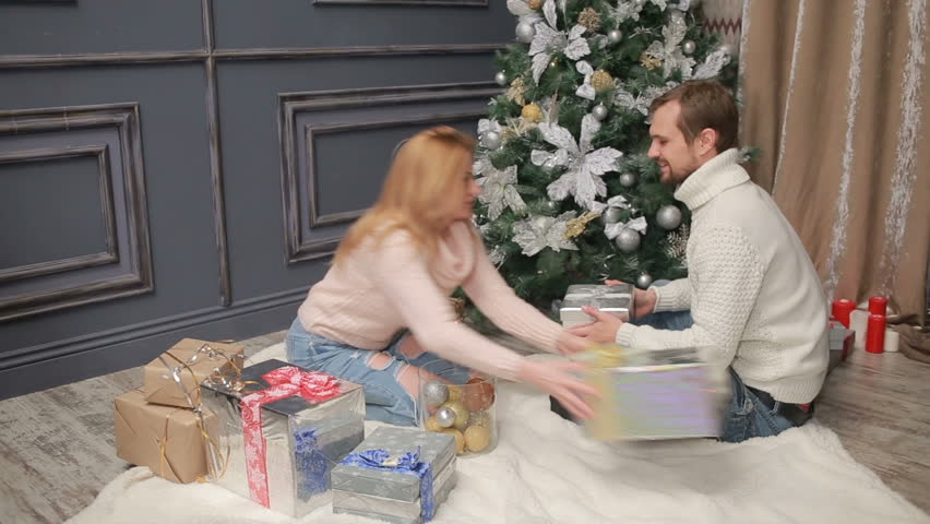 young married couple arranges gifts under the christmas tree