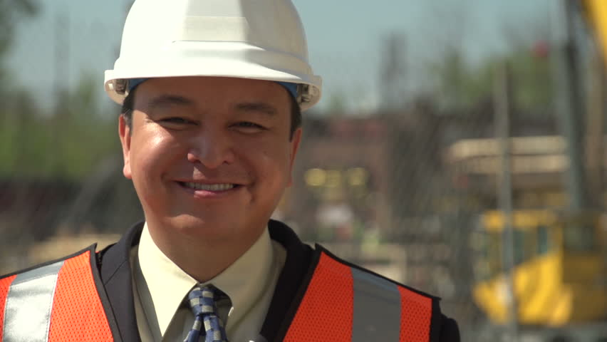 Business man on a construction site, close up looking at camera