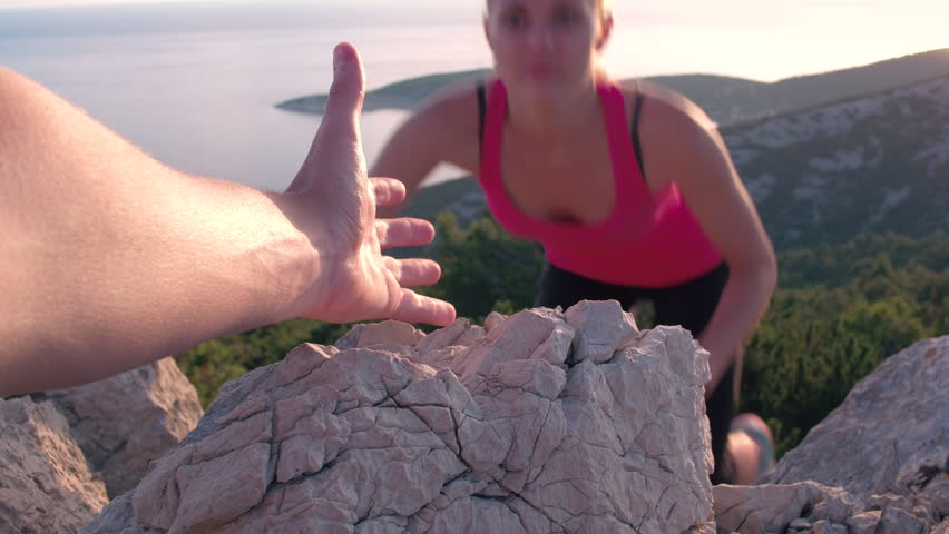 Closeup of a male's hand stretching out and helping female friend reach the mountain top by pulling her up. POV of a man giving hand to a woman climbing on the mountain and helping her reach the top | Shutterstock Video #22213453