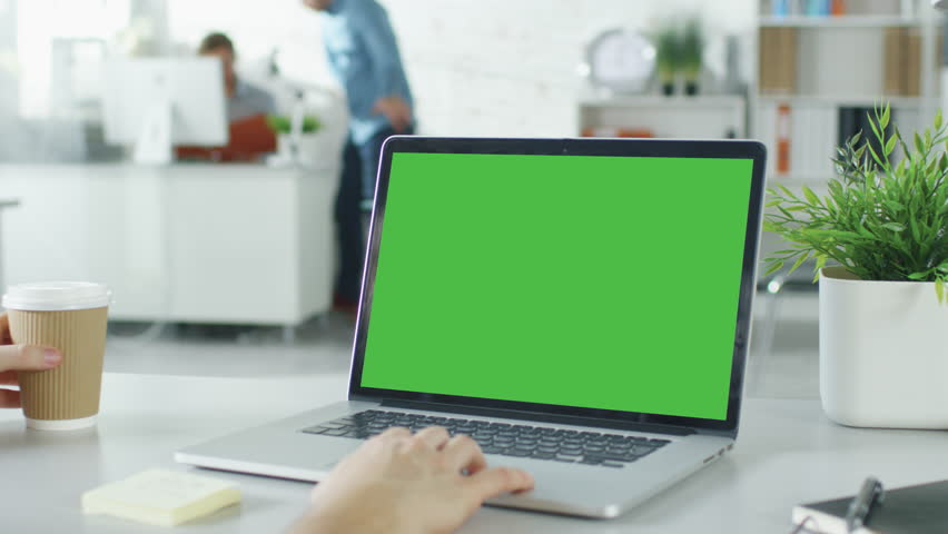 Close-up of a Man's Hands Working on Green Screen on a Laptop. In Background Blurred and Brightly Lit Office where One Man Approaches the Other and They Have Discussion. Shot on RED EPIC (uhd).