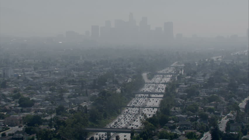 Aerial shot of a smoggy, overcast city with a major multi-lane freeway and skyline circa 2009