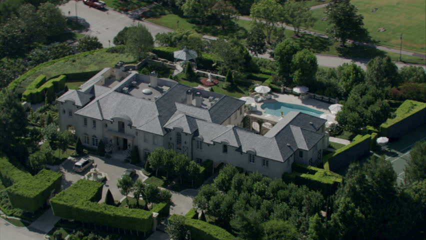 aerial view of an expansive 19th century mansion with manicured landscaping, pool, and surrounding property circa 2009